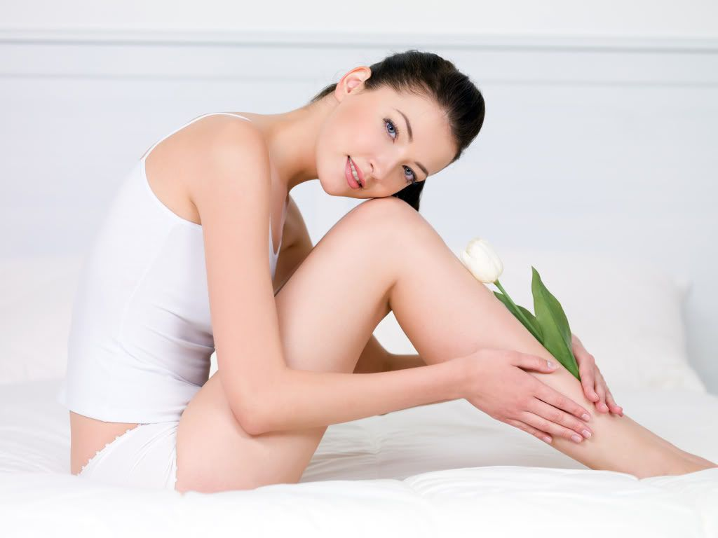 Beautiful young woman with white tulip on her attractive perfect legs - indoors Triệt lông
